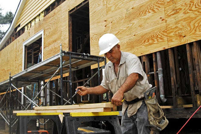 In this 2006 file photo, Raphael Iqarza works on restoring a historic home in Pass Christian, Miss. The Louisiana State Licensing Board for Contractors offers tips for people needing to hire a contractor.