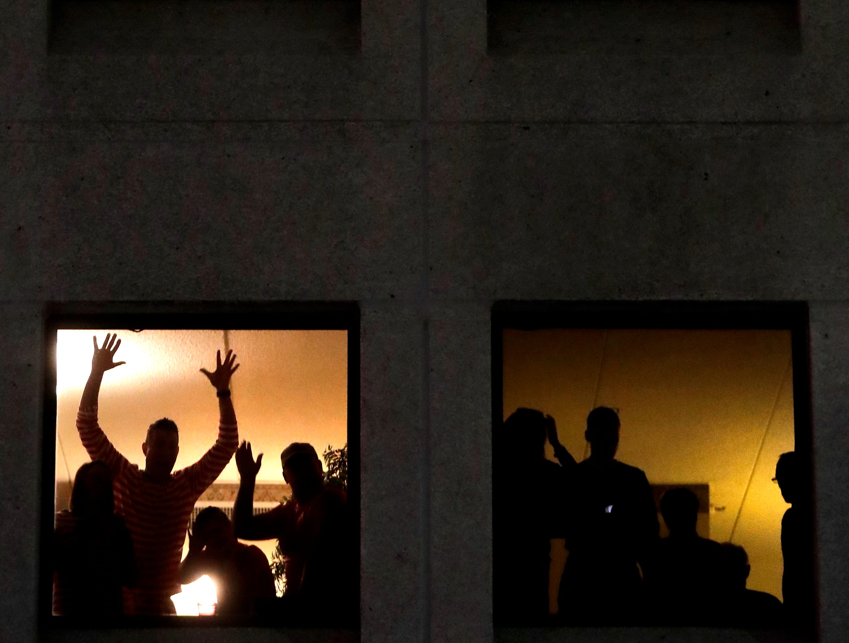 """Spectators watch fro the windows of the Red Lion Paper Valley Hotel during the 48th Annual Downtown Appleton Christmas Parade on Tuesday, Nov. 20, 2018 in Appleton, Wis. This year's theme was """"Home for the Holidays."""" Wm. Glasheen/USA TODAY NETWORK-Wisconsin."""