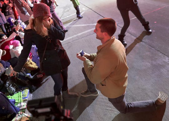 Bryce Sternhagen gets on one knee to propose to Samantha Cucci during Tuesday's Downtown Appleton Christmas Parade.