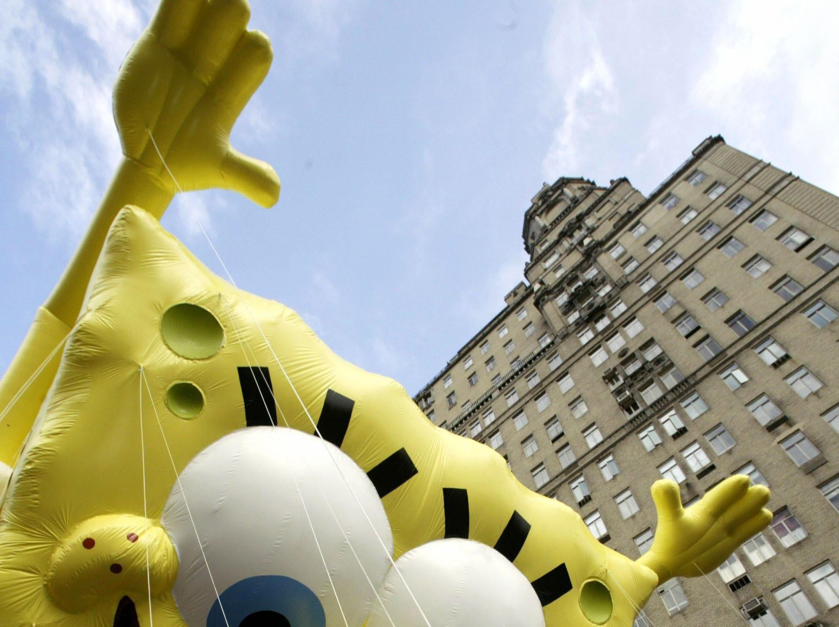 Gwen Deforte unwinds the line connected to the hand of Spongebob Squarepants as the baloon is prepared for its' first Macy's Parade in New York Thursday, Nov. 25, 2004. Thousands of people lined the streets to see the Thanksgiving Day tradition and to cheer on some newcomers like Spongebob.  (AP Photo/Gregory Bull)