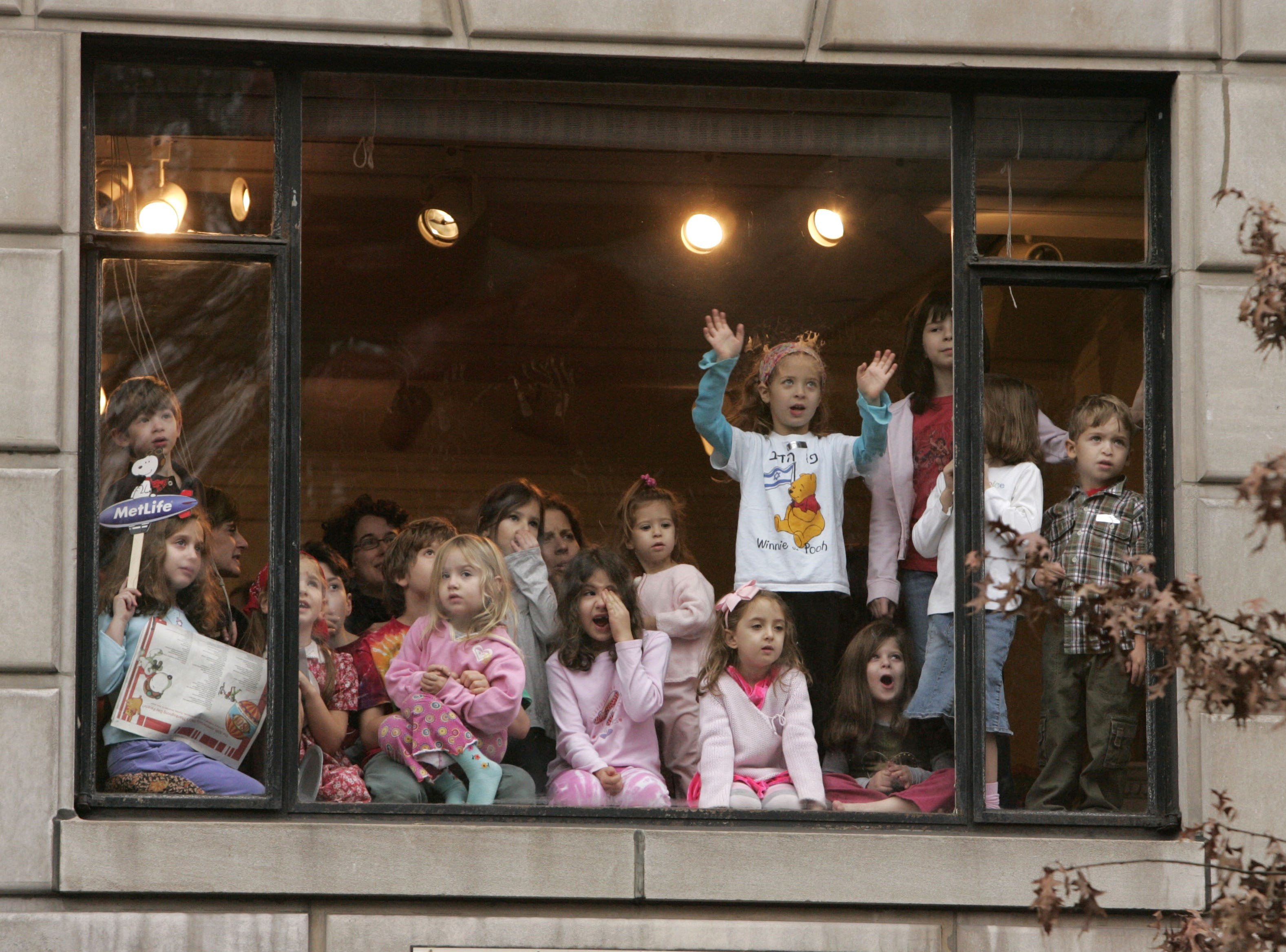 A group of children watch the Macy's Thanksgiving Day Parade go by from an apartment window on Central Park West Thursday, Nov. 23, 2006 in New York. (AP Photo/Julie Jacobson)