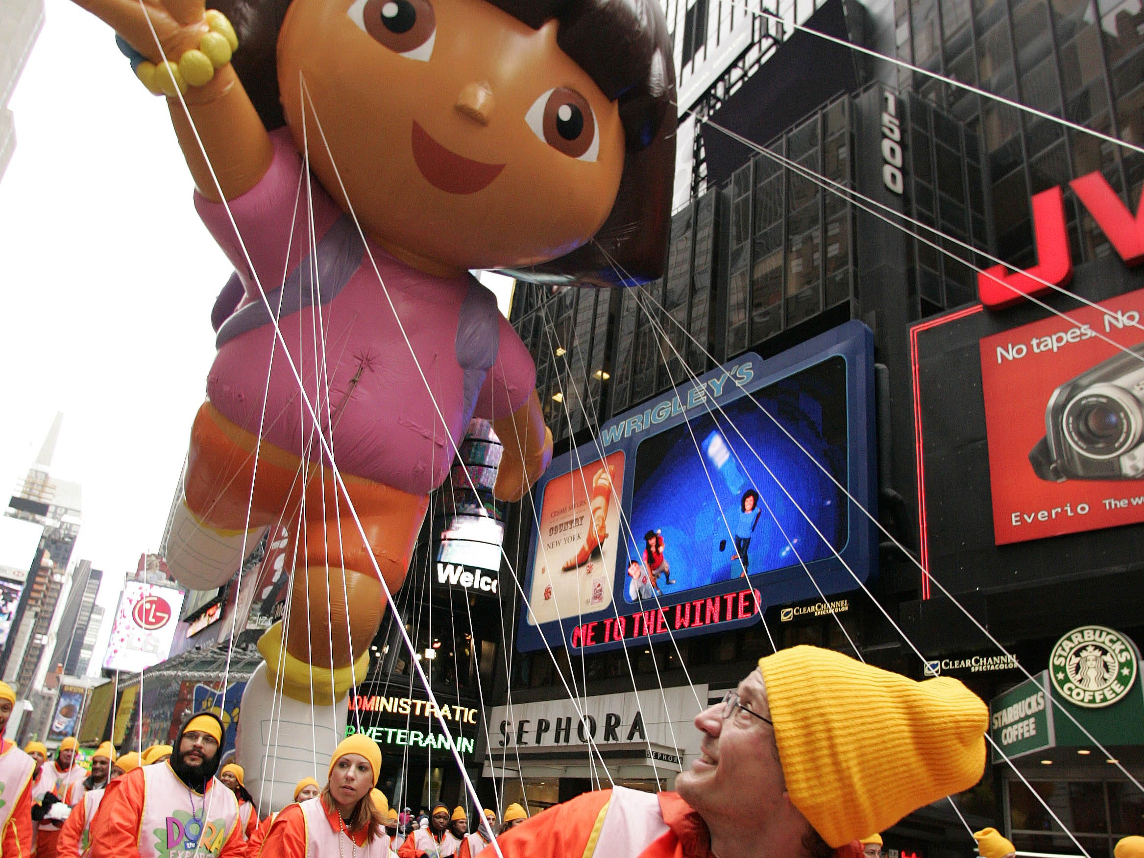 ** FILE ** Robert Segal, of Brooklyn, helps pull a Dora the Explorer balloon through Times Square during the Macy's Thanksgiving Day Parade in this Thursday, Nov. 24, 2005 file photo in New York. There's good news for fans of the Macy's Thanksgiving Day Parade: A helium shortage that has rattled markets around the world during 2006 will not have a deflating effect on the annual New York holiday tradition. (AP Photo/Julie Jacobson)
