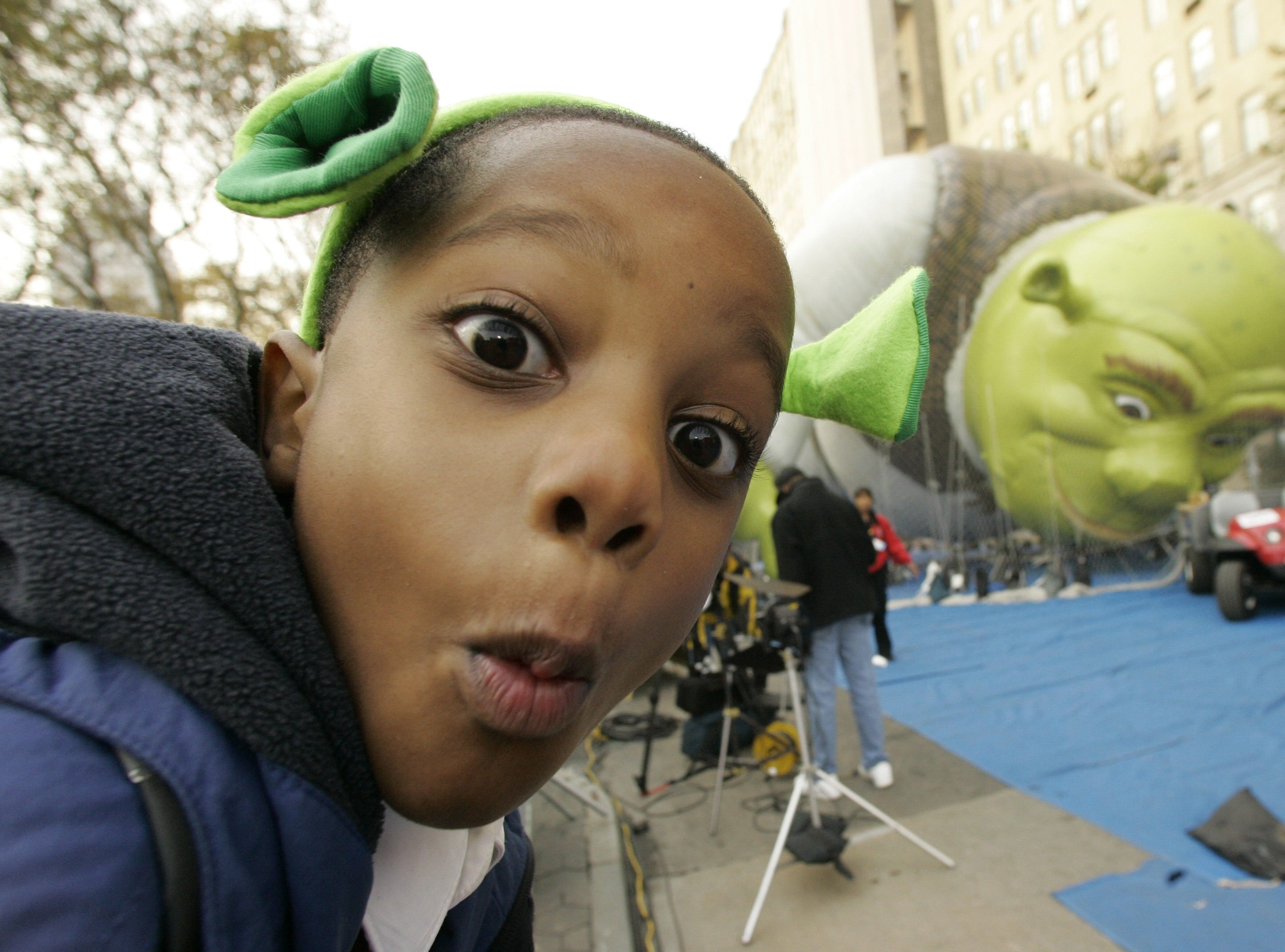 """Maurace Morris, 6, of the Brooklyn borough of New York, plays for the camera near the """"Shrek"""" balloon during Macy's 81st Annual Thanksgiving Day Parade """"Inflation Eve,"""" Wednesday, Nov. 21, 2007 in New York. Preparations started Wednesday afternoon as giant balloons and many smaller inflatables were filled with a helium air mixture for the Thanksgiving parade march down 5th Ave. (AP Photo/Mary Altaffer)"""