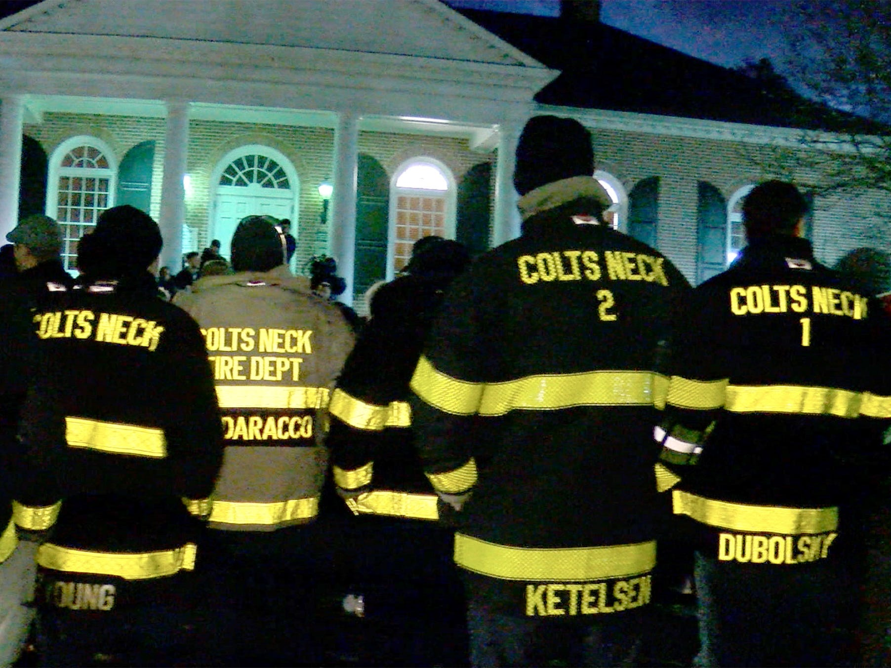 Colts Neck firefighters gather outside the Colts Neck Town Hall Wednesday night, November 21, 2018, for a vigil to remember the Caneiro family killed in a house fire the previous day.