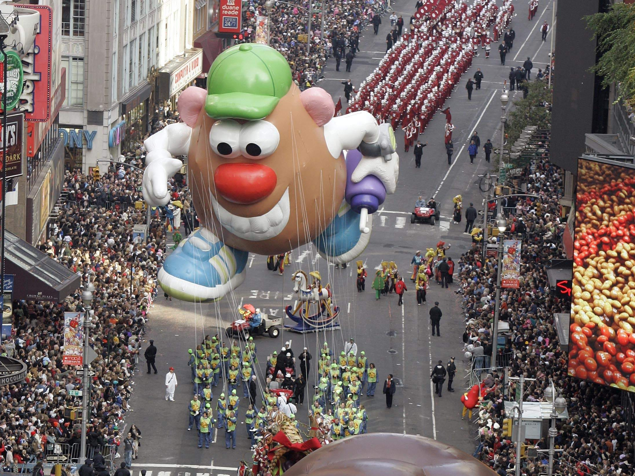 The Mr. Potato Head balloon follows Dora The Explorer down Broadway during the Macy's Thanksgiving Day parade in New York, Thursday, Nov. 22, 2007.     (AP Photo/Jeff Christensen)
