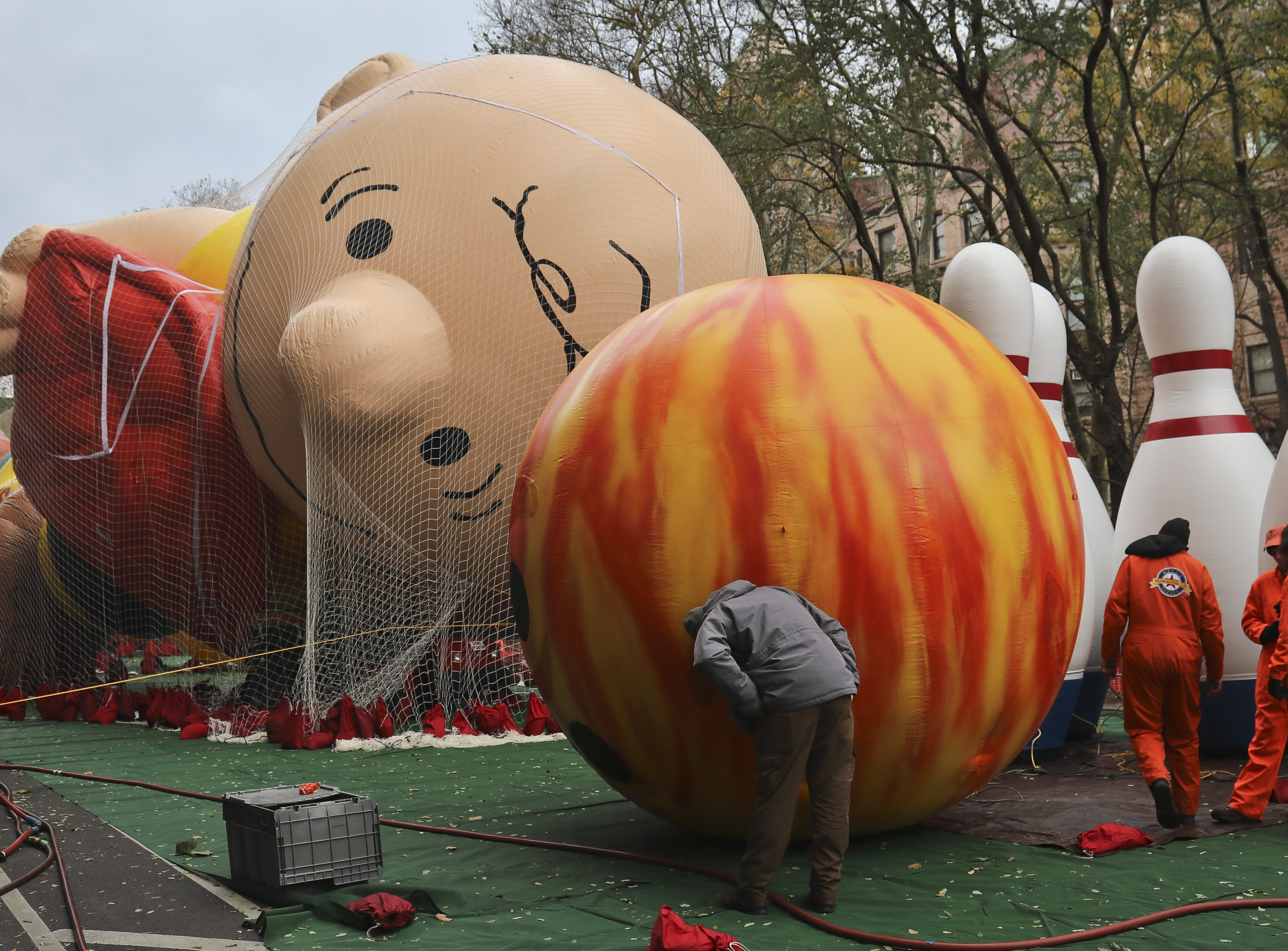 Giant character balloons, including Charlie Brown and Go Bowling, are inflated the night before their appearance in the 92nd Macy's Thanksgiving Day parade, Wednesday Nov. 21, 2018, in New York. (AP Photo/Bebeto Matthews)