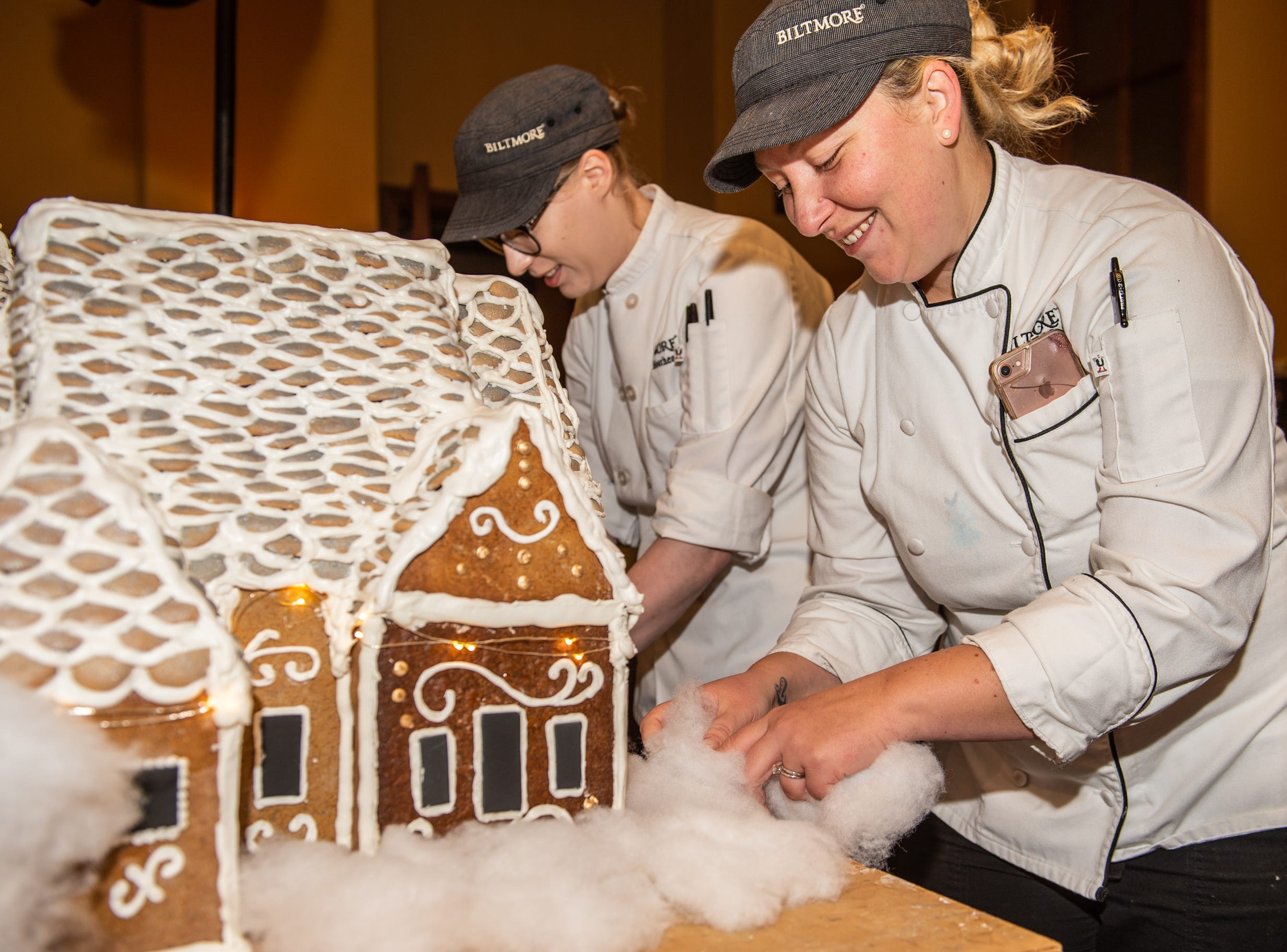 Biltmore pastry chef Julie Scheibel, right, and pastry demi chef Megan Moorhead, left, position cotton snow around the base of the gingerbread house in the Biltmore House kitchen the morning of Nov. 2, 2018.
