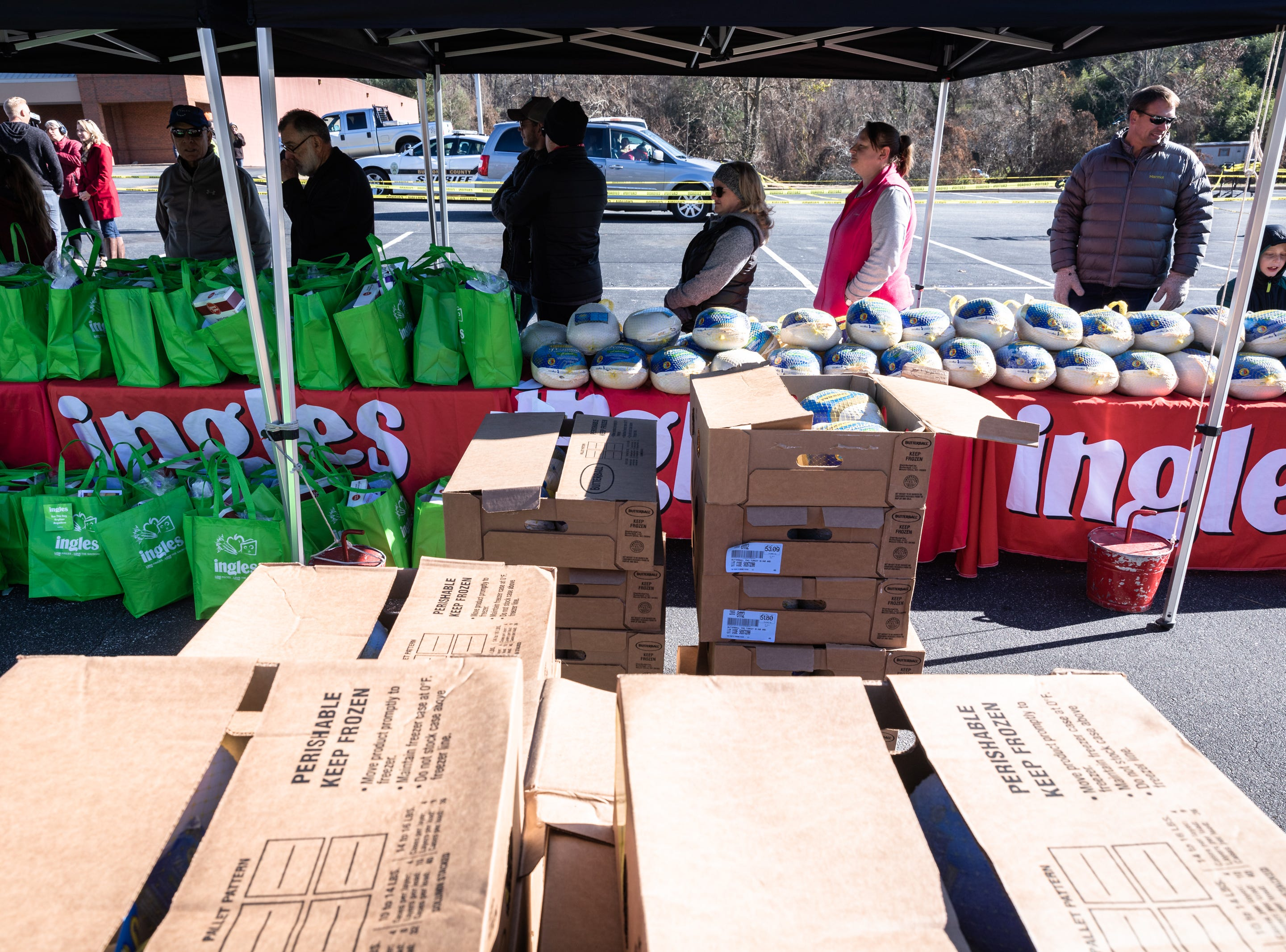 Volunteers with Eblen Charities line up with Thanksgiving meals to bring to clients' vehicles at Ingles in the South Forest Shopping Center, during their annual turkey giveaway Nov. 21, 2018. More than 13,000 meals were provided to nearly 1,300 families this year.