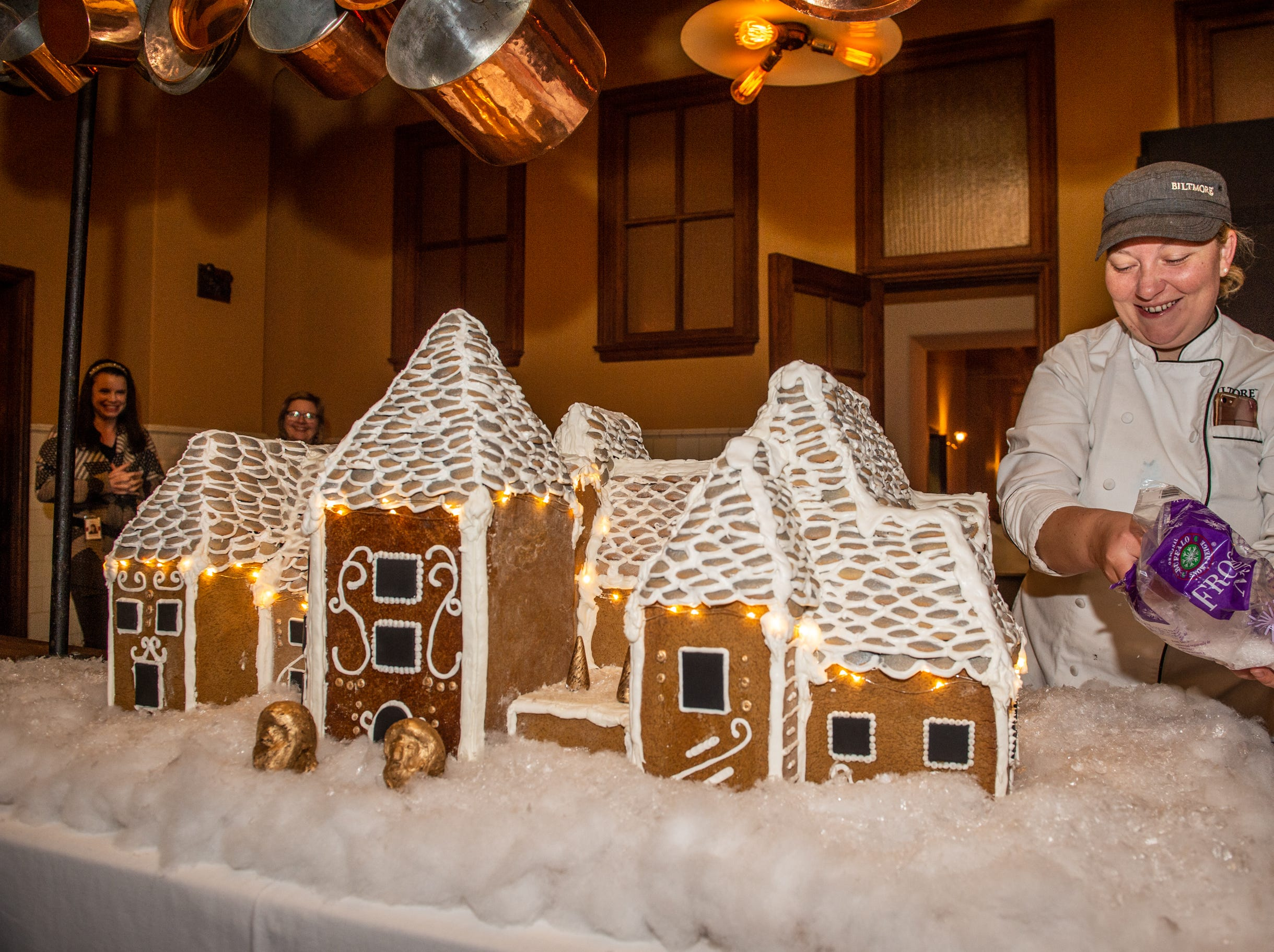 Biltmore pastry chef Julie Scheibel tops the cotton snow with sparkling flakes around the gingerbread house in the Biltmore House kitchen on the morning of Nov. 2, 2018.