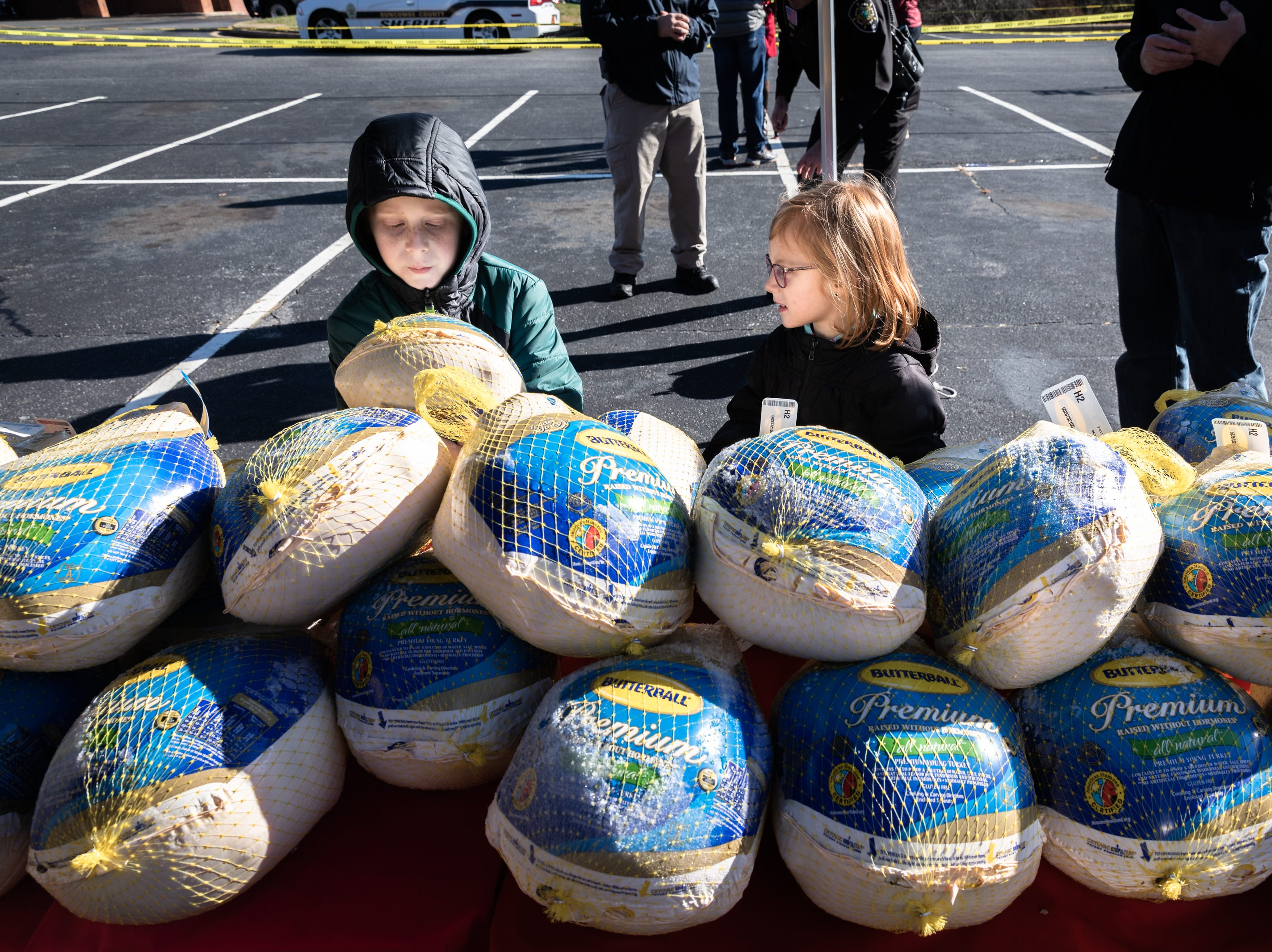 Caleb Gordon, 9 and his sister Hannah Gordon, 7, of Akron Ohio, pick out turkeys to hand to Eblen Charities clients as they volunteer with their family at Ingles in the South Forest Shopping Center, during the annual turkey giveaway Nov. 21, 2018. More than 13,000 meals were provided to nearly 1,300 families this year.