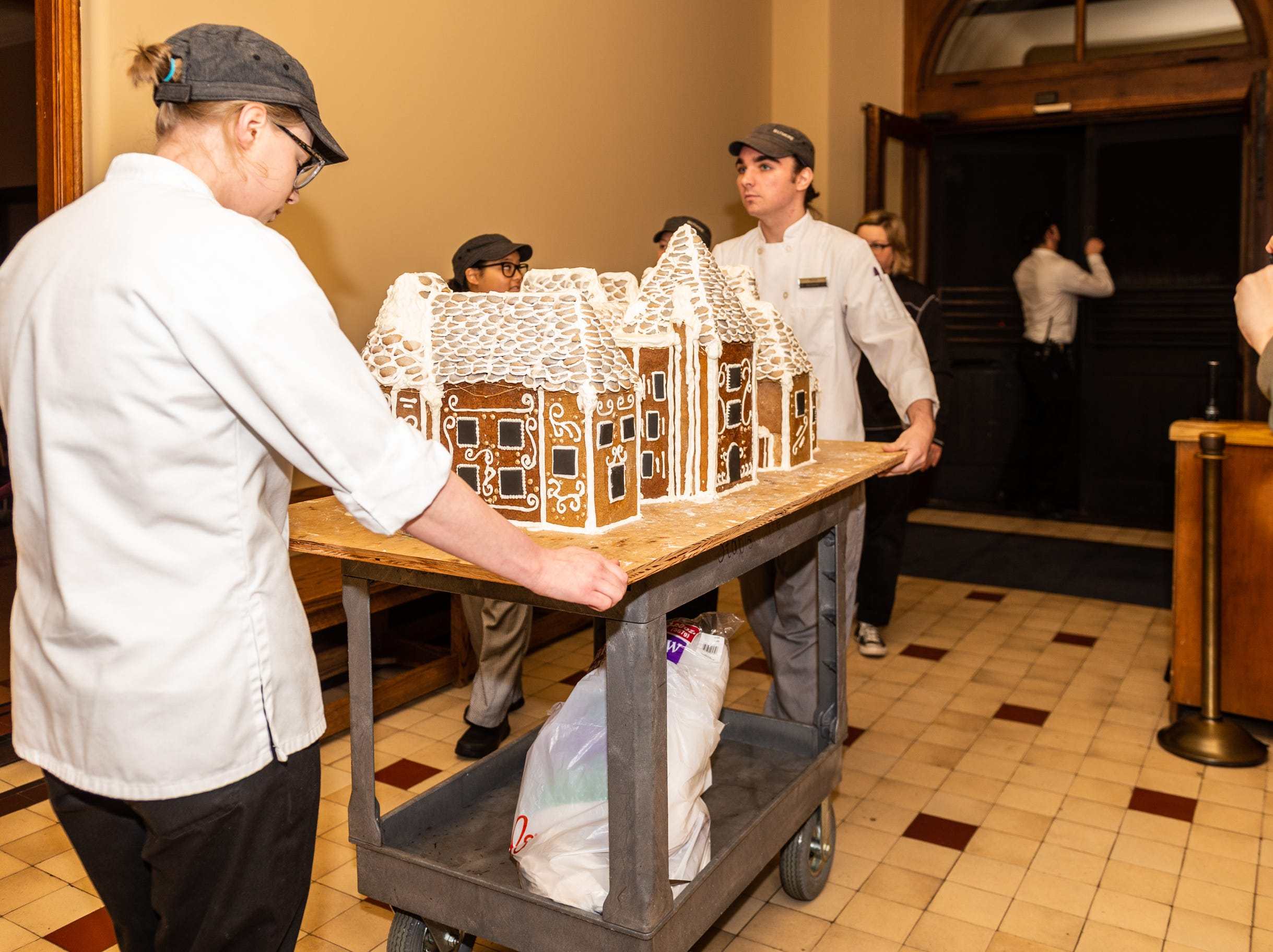 Biltmore pastry demi chef Megan Moorhead, left, and pastry cook Deron Noel maneuver the gingerbread house through a hallway in Biltmore House in the predawn dark Nov. 2, 2018.