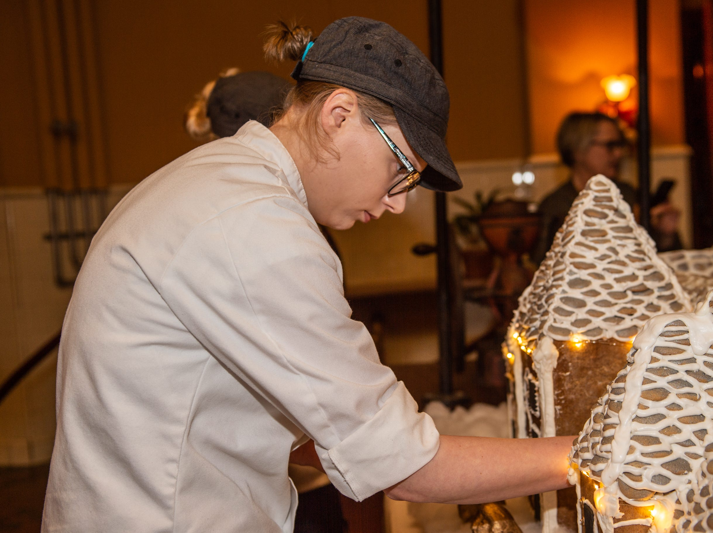 Biltmore pastry demi chef Megan Moorhead helps put the finishing touches on the gingerbread house in the Biltmore House kitchen on the morning of Nov. 2, 2018.
