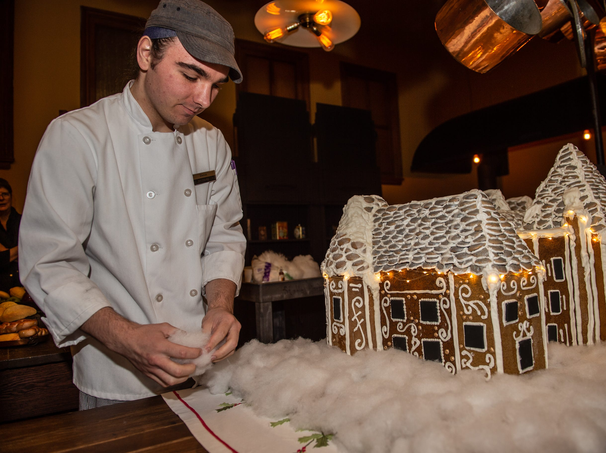 Biltmore pastry cook Deron Noel helps put the finishing touches on the gingerbread house in the Biltmore House kitchen on the morning of Nov. 2, 2018.