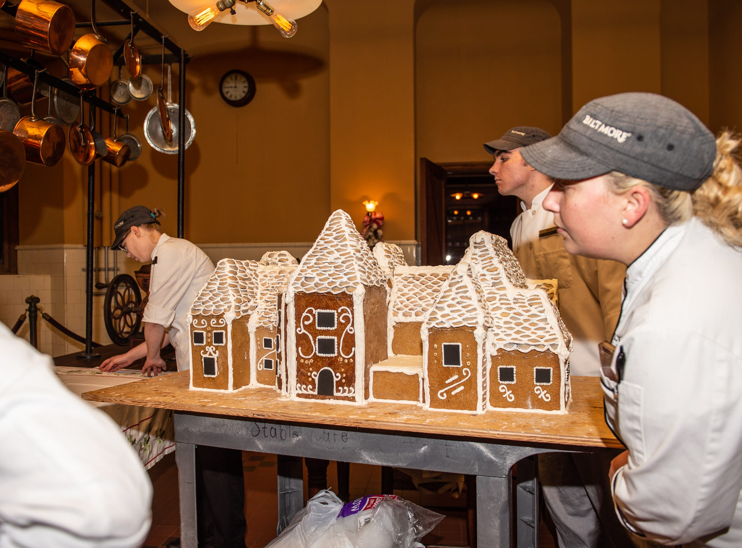 Biltmore pastry chef Julie Scheibel, right, helps move the gingerbread house into place in the Biltmore House kitchen the morning of Nov. 2, 2018.