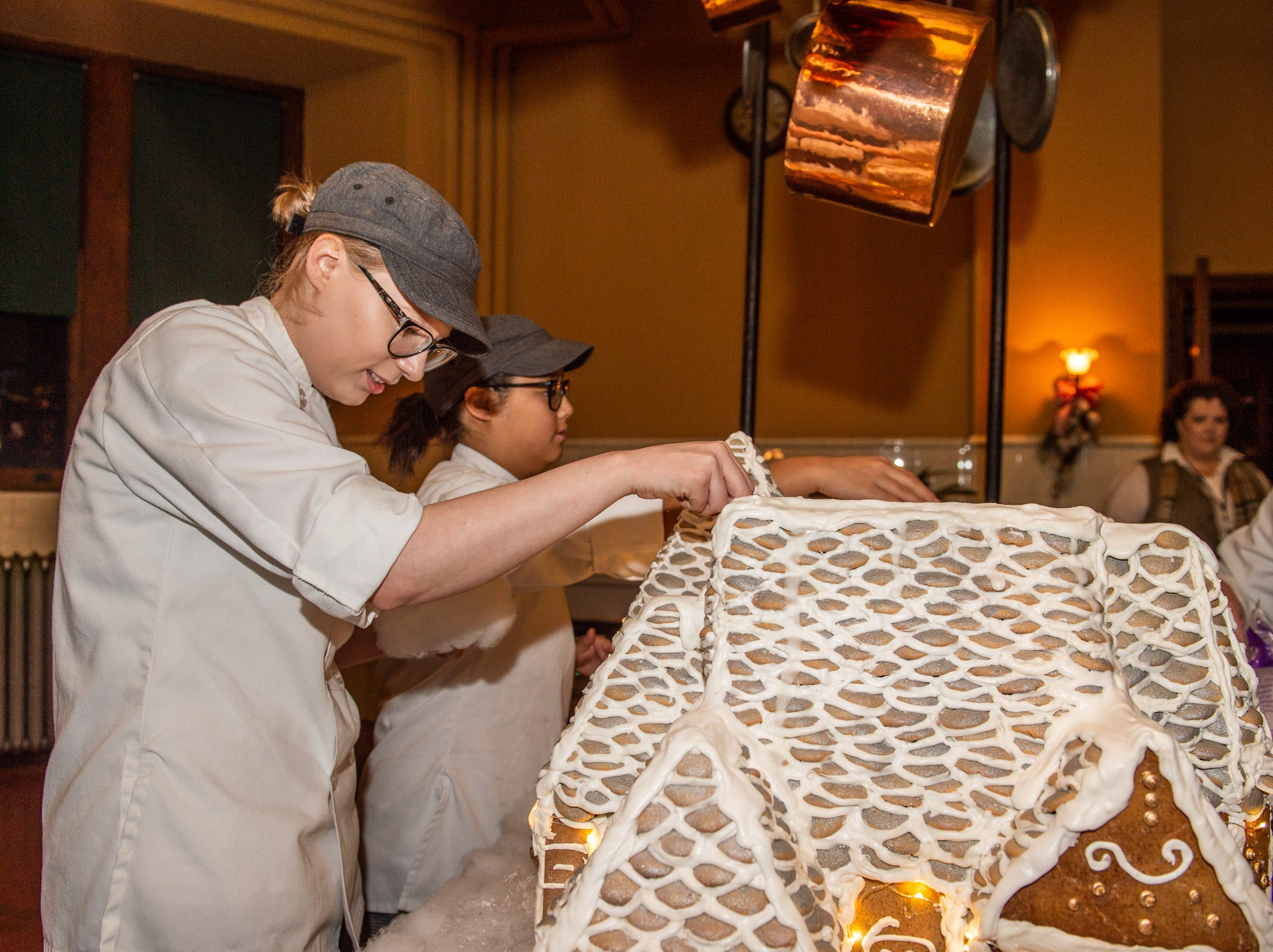Biltmore pastry demi chef Megan Moorhead, left, and pastry cook Kayla Breedlove help put the finishing touches on the gingerbread house in the Biltmore House kitchen on the morning of Nov. 2, 2018.