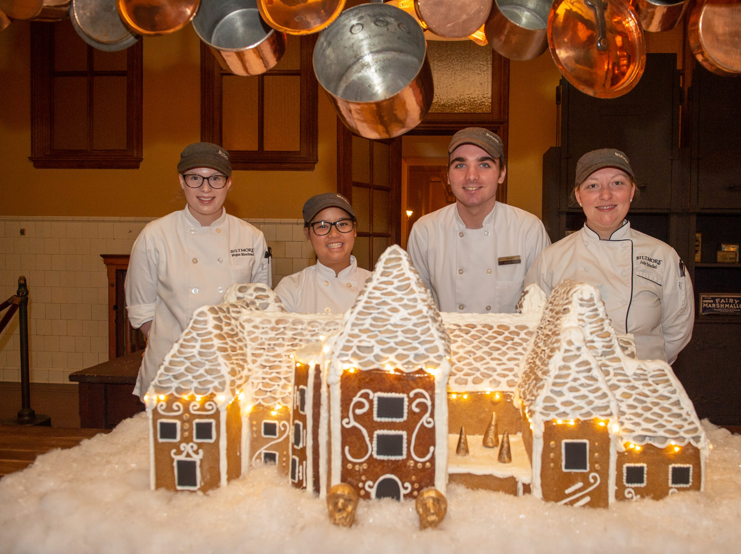 From left, Biltmore pastry demi chef Megan Moorhead, pastry cooks Kayla Breedlove and Deron Noel and pastry chef Julie Scheibel stand behind the completed gingerbread house in the Biltmore Estate kitchen the morning of Nov. 2, 2018. The lights are new this year, an addition Scheibel cooked up.