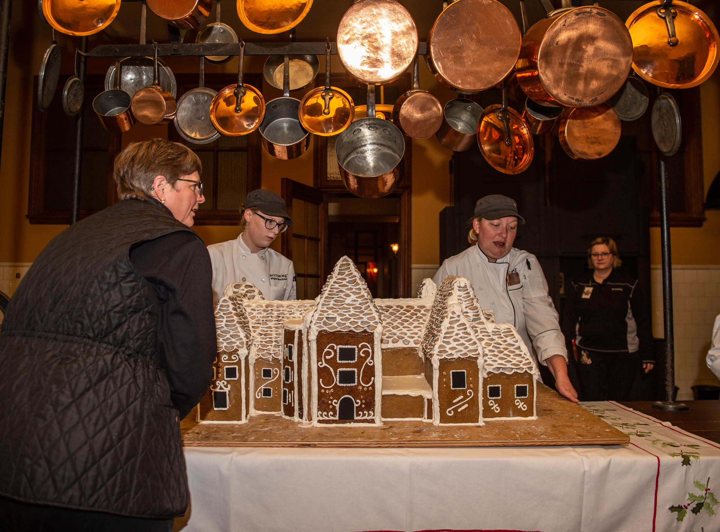 Biltmore floral staffer Mark Quark, left, helps pastry chef Julie Scheibel, right, and pastry demi chef Megan Moorhead, center, position the gingerbread house in the Biltmore House kitchen the morning of Nov. 2, 2018.