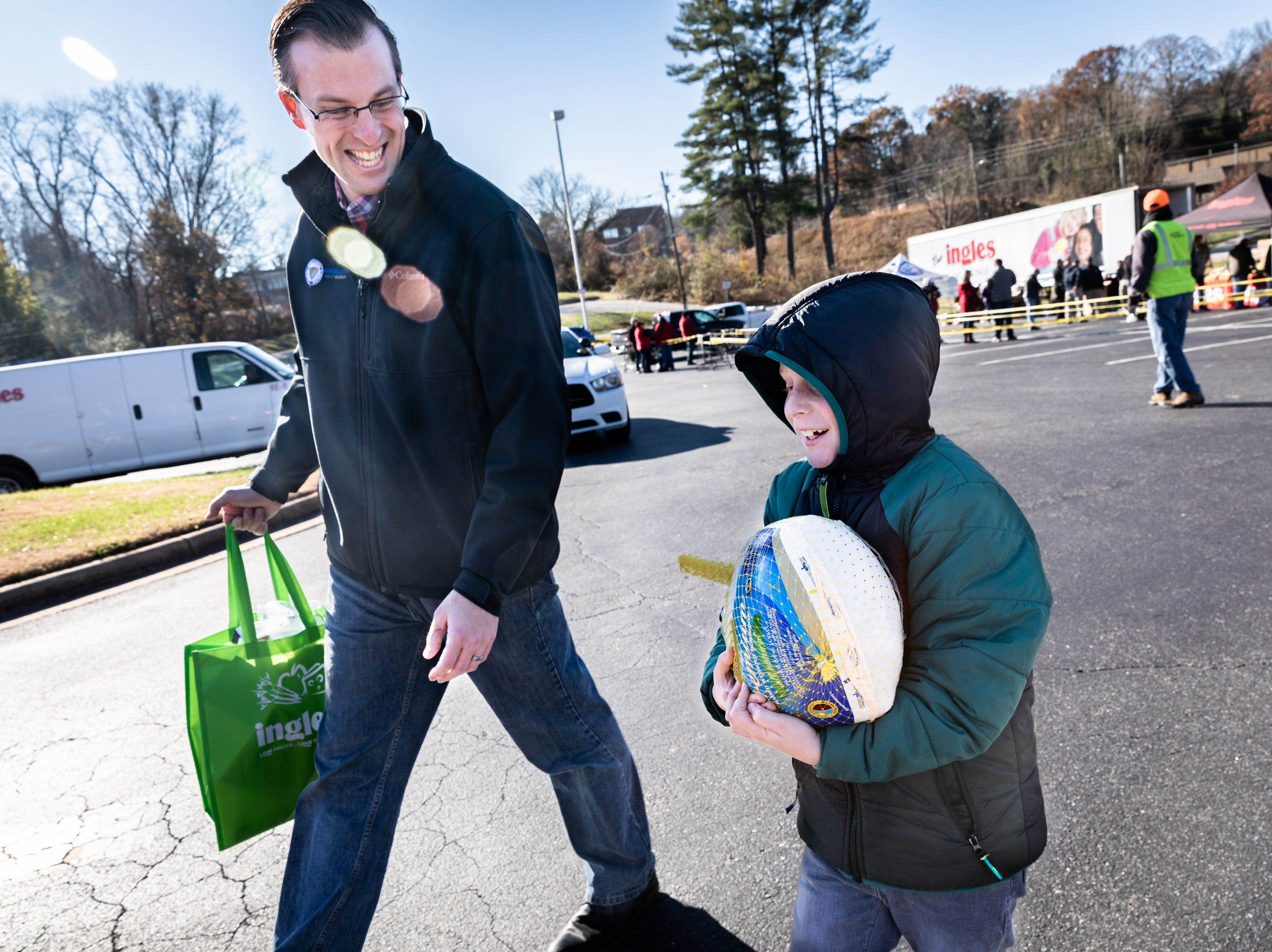 Josh Gordon and his son Caleb Gordon, 9, of Akron, OH, carry a Thanksgiving meal to the car of an Eblen Charities client at Ingles in the South Forest Shopping Center, during the annual turkey giveaway Nov. 21, 2018. More than 13,000 meals were provided to nearly 1,300 families this year.