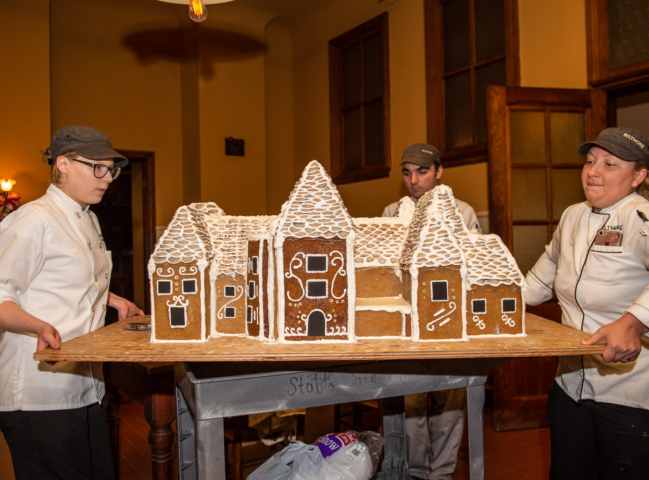 Biltmore pastry chef Julie Scheibel, right, pastry cook Deron Noel, center, and pastry demi chef Megan Moorhead, left, move the gingerbread house into place in the Biltmore House kitchen the morning of Nov. 2, 2018.