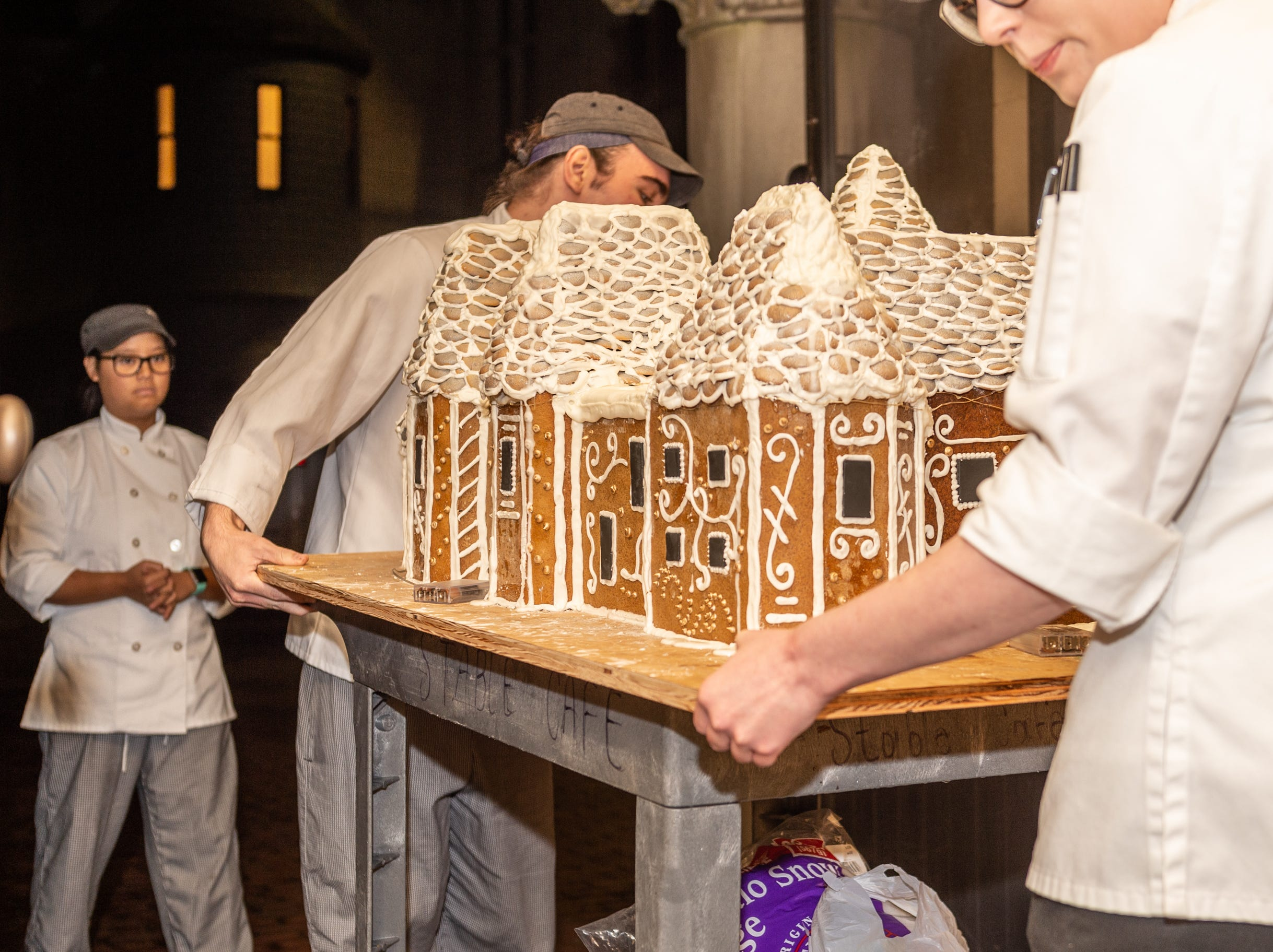 Biltmore pastry cook Deron Noel, center, and pastry demi chef Megan Moorhead, right, maneuver the gingerbread house through a hallway in Biltmore House in the predawn dark Nov. 2, 2018, as pastry cook Kayla Breedlove follows.