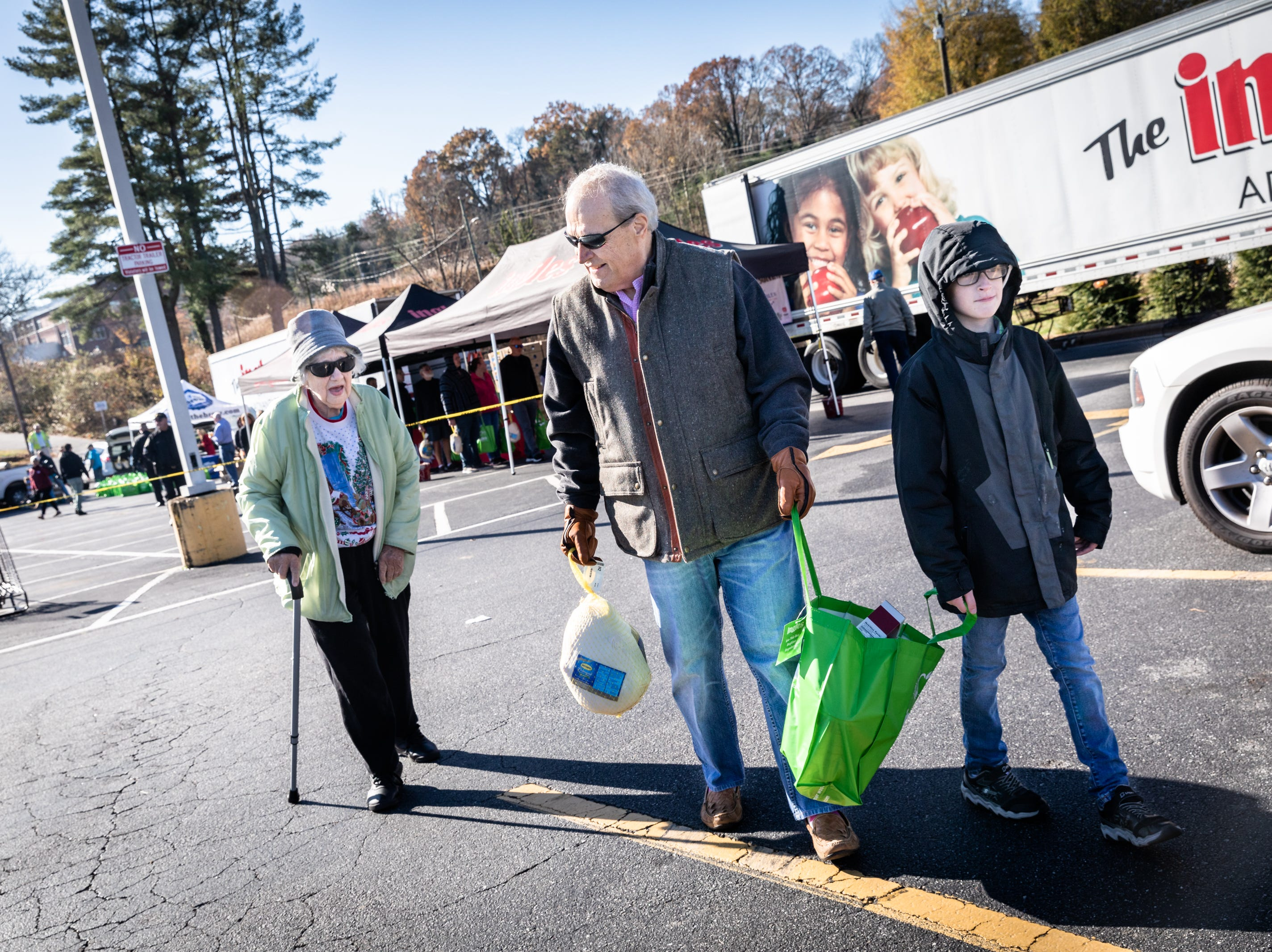 Steve Gordon and his grandson Luke Gordon, 11, carry a Thanksgiving meal with Hettie Brookens, 87, of Swannanoa  to her car at Ingles in the South Forest Shopping Center, during the annual turkey giveaway Nov. 21, 2018. More than 13,000 meals were provided to nearly 1,300 families this year.
