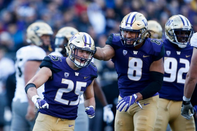 Washington Ben Burr-Kirven (25) is congratulated by Benning Potoa'e after a tackle against the Colorado last month. Burr-Kirven is second in all of college football in tackles, and likely will re-take the top spot after Friday's Apple Cup.