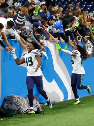 Seattle Seahawks Shaquem Griffin (49) and Shaquill Griffin (26) shake hands with fans after an Oct. 28 win in Detroit.