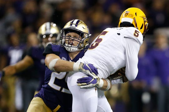 Huskies linebacker Ben Burr-Kirven (25) tackles Arizona State quarterback Manny Wilkins during a game this season in Seattle. Burr-Kirven has 145 tackles through 11 games.