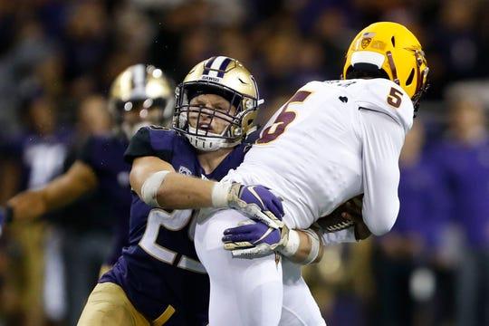 Huskies linebacker Ben Burr-Kirven (25) tackles Arizona State quarterback Manny Wilkins during a game this season in Seattle. Burr-Kirven has 145 tackles through 11 games.