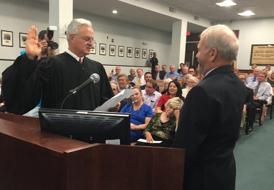 Circuit Judge David Dugan, left, administers the oath of office to County Commissioner Curt Smith, as Smith begins his second four-year term in District 4.