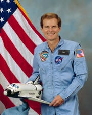Official portrait of congressman Bill Nelson in his role as a payload specialist on NASA's STS 61-C space shuttle mission. He is in the blue shuttle flight suit, holding a model of the shuttle with an American flag behind him.