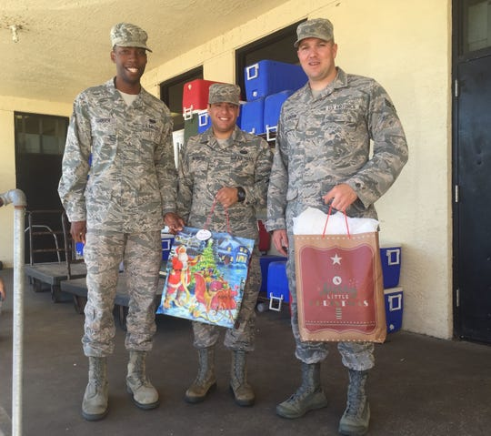In a December 2017 photo, Staff Sergeant Frederick Scarber, left, and Senior Airmen Aldonys Reynoso and Nicholas Creighton, who volunteer with Meals on Wheels, dropped off Reaching Out Holiday Fund gifts with the meals on their route. The men, stationed at Patrick Air Force Base, say volunteering has changed their lives and, hopefully, the lives of those they meet. Britt Kennerly/ FLORIDA TODAY