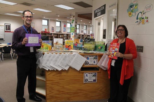 Librarian Beth Willoughby and Municipal Alliance Member, Karl Geiger with the books donated.