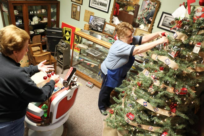 Dee Smith, left, and Teresa Abrams decorate the Post Office tree for the Warsaw Festival of Trees in the Walhonding Valley Historical Society Museum on Tuesday. The festival open on Saturday.