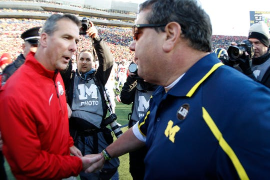 Ohio State head coach Urban Meyer and Michigan and head coach Brady Hoke post game handshake after Ohio's 42-41 win in Ann Arbor on Saturday, November 30,  2013.