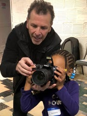 Gaal Karp works with Shania on using a camera at Cass Community Social Services World Building in Detroit on Oct. 20, 2018.