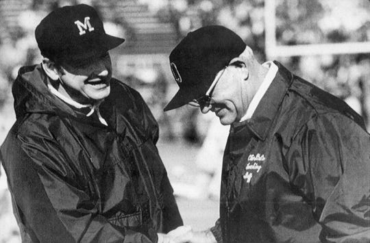 Michigan football coach Bo Schembechler, left, meets with Ohio State coach Woody Hayes in this undated photo.