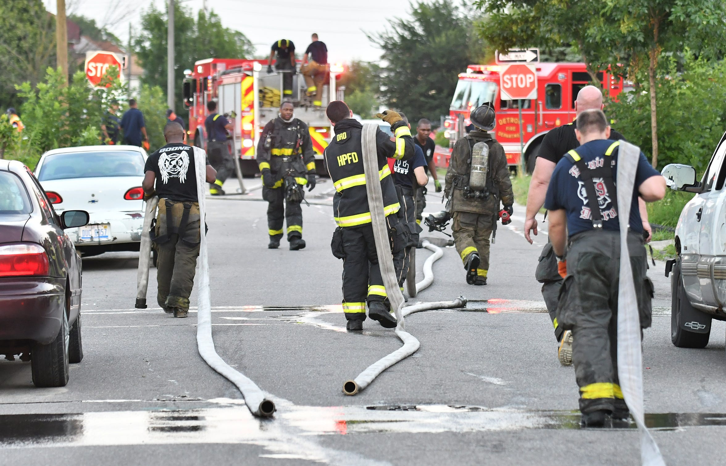 Detroit and Highland Park firefighters pull hoses at the scene of a fire at an occupied dwelling in Detroit in August.