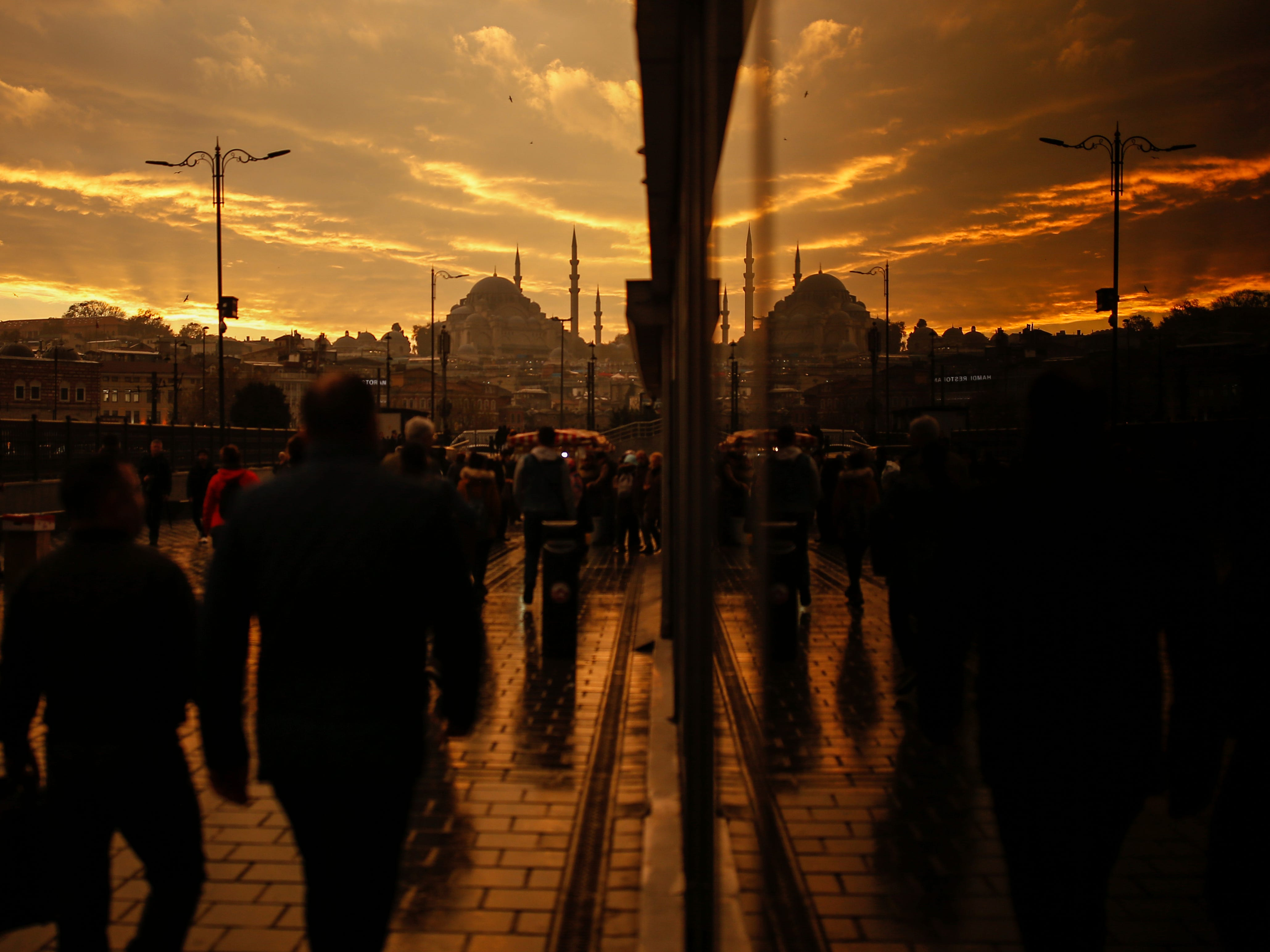 Backdropped by the iconic Suleymaniye Mosque in Istanbul, people are reflected in a glass as they walk on a bridge over the Golden Horn, Wednesday, Nov. 21, 2018.