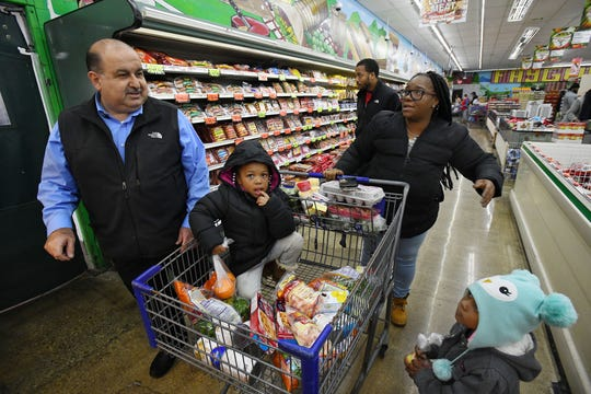 Sam Hamama helps Anette Reese with grandchildren Popo, 3 and Kayla, 3 looking for an item while working at Family Foods Market in Harper Woods, Michigan on November 20, 2018.