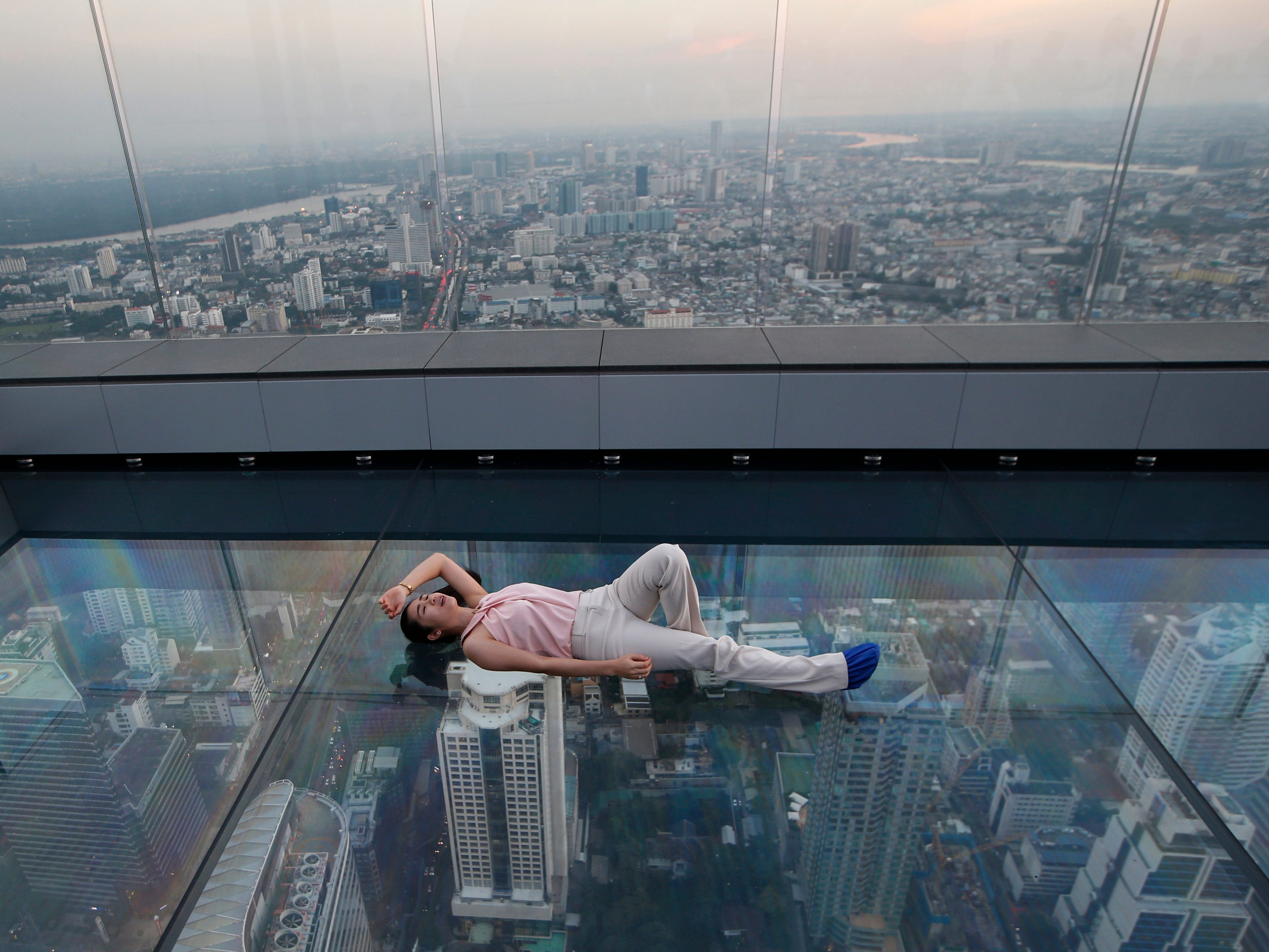 A woman lies on the glass bottom deck of the King Power Mahanakhon building high above Bangkok, Thailand, Wednesday, Nov. 21, 2018. The King Power Mahanakhon building, currently Thailand's tallest at 314 meters (1,030 feet) with 78 floors, has a 360-degree view of Bangkok.