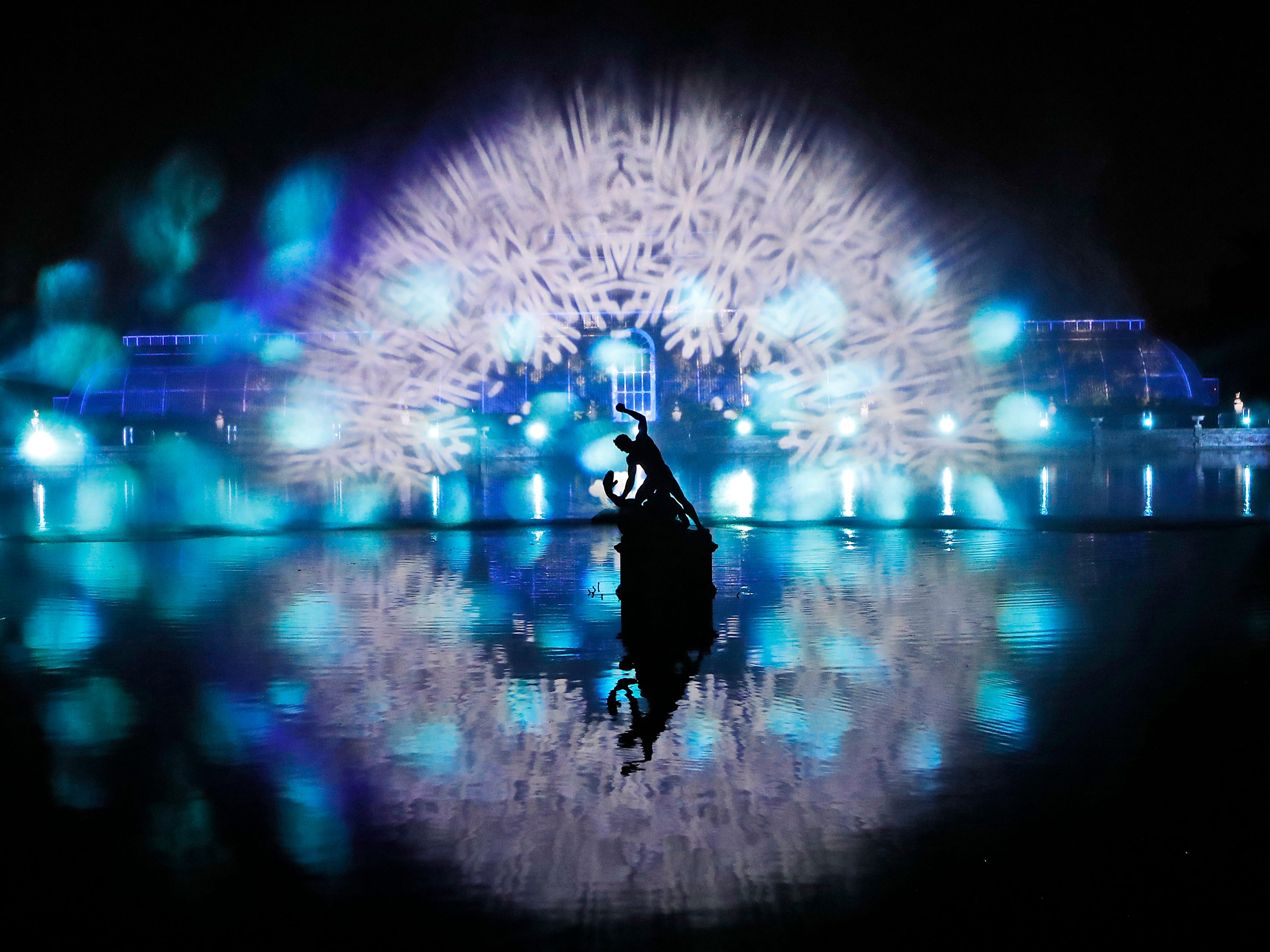 A Grand Finale illuminates the Palm House by laser light as part of the illuminated trail through Kew Gardens magnificent after-dark landscape, lit up by over one million twinkling lights in London, Wednesday, Nov. 21, 2018.