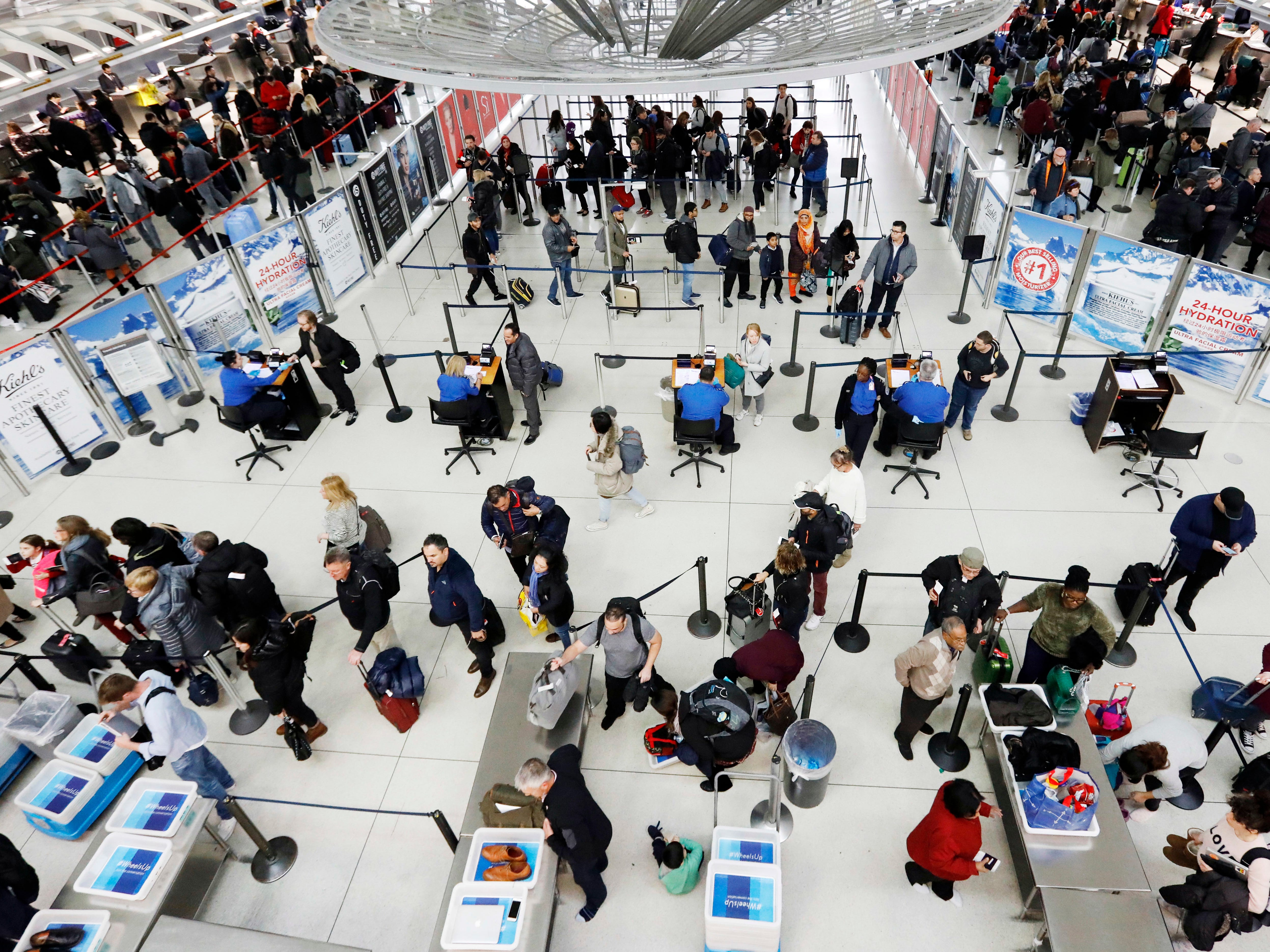 Travelers line up for a security checkpoint at John F. Kennedy International Airport, Wednesday, Nov. 21, 2018, in New York. The airline industry trade group Airlines for America expects that Wednesday will be the second busiest day of the holiday period behind only Sunday, when many travelers will be returning home after Thanksgiving.