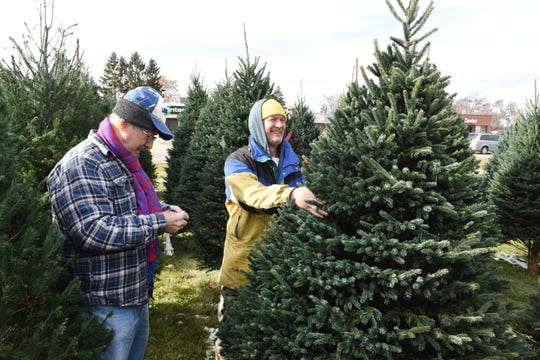 Paul LaTorre (left), owner of Paul's Christmas Trees of Kalkaska, tags trees with salesman Thayne Lentz (right) at his tree lot located along John R. Road near 13 Mile Road in Madison Heights on Wednesday, November 21, 2018.