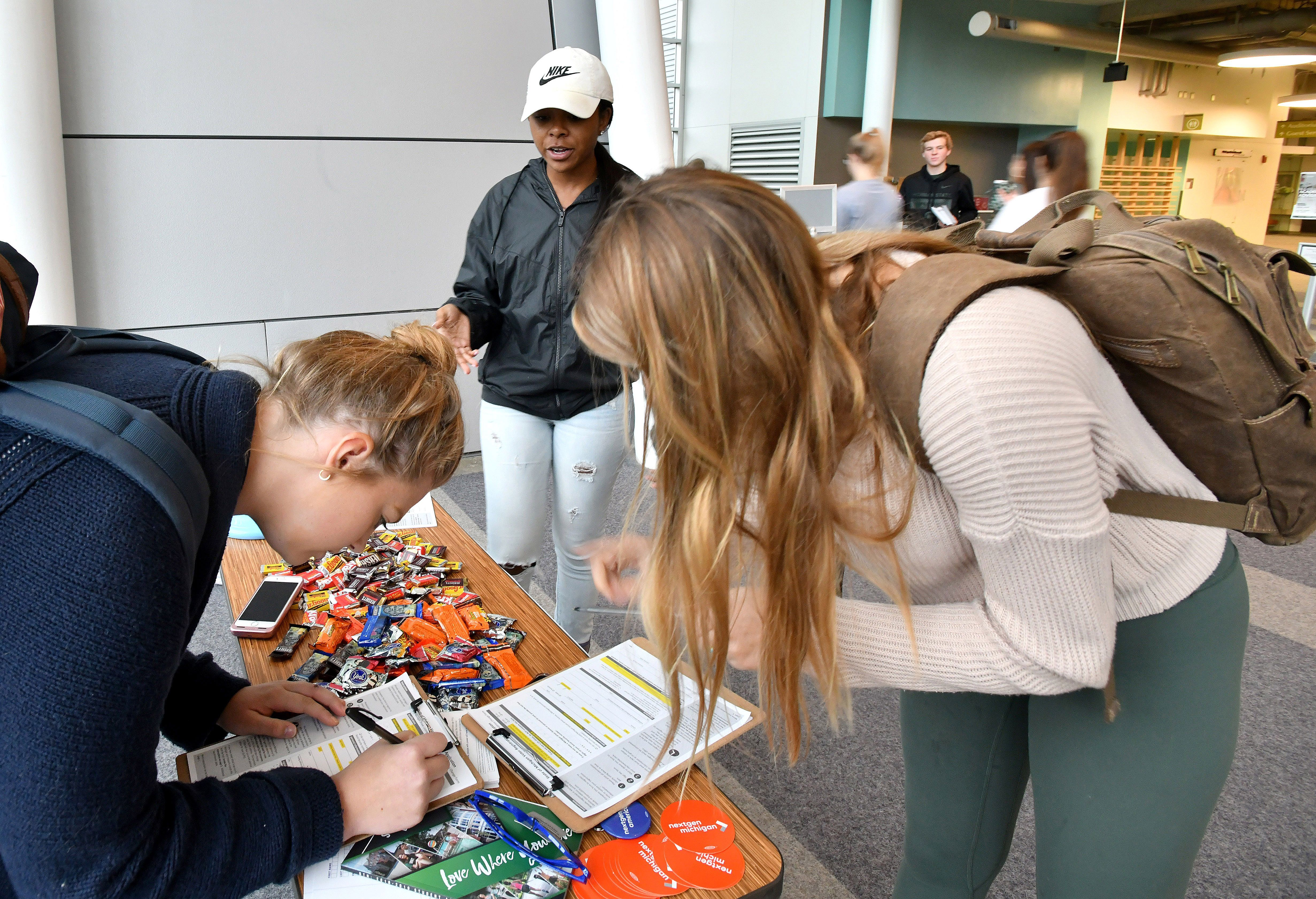 Shanel Thomas (center) of NextGen America oversees Michigan State University students registering to move their registration to East Lansing so they can vote locally in the midterm election.