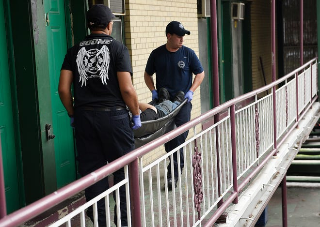 Detroit firefighters Darrell Tucker, left, and Matthew Ponce carry a man who overdosed and died on drugs at the Bali Motel in Detroit on July 24.