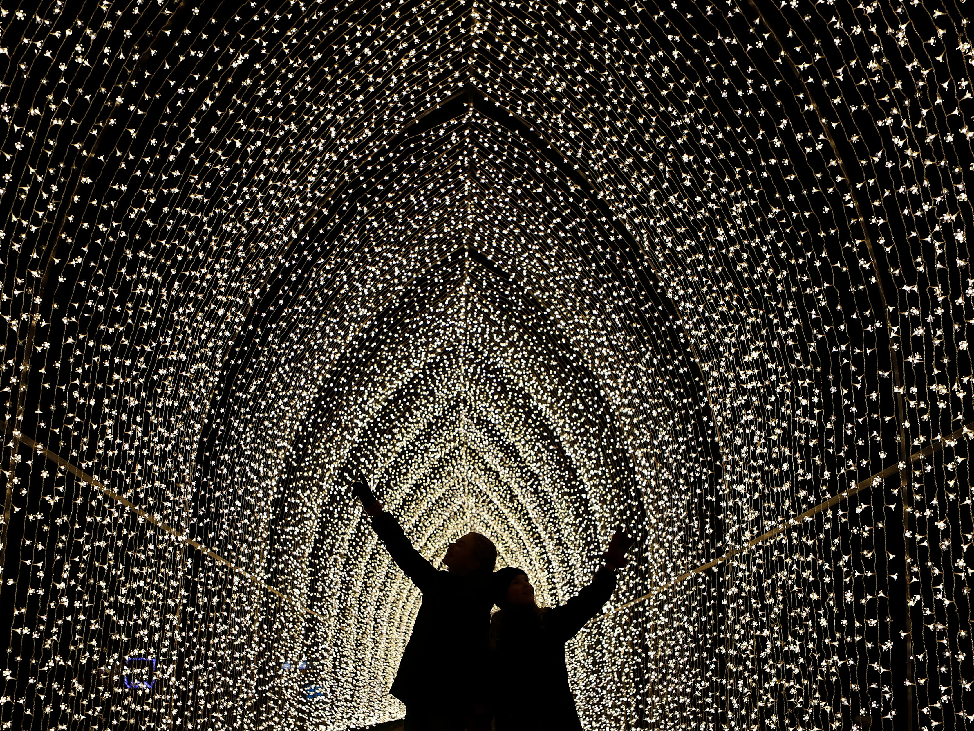 Children walk through the Cathedral of Light as part of the illuminated trail through Kew Gardens magnificent after-dark landscape, lit up by over one million twinkling lights in London, Wednesday, Nov. 21, 2018.