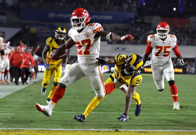 Kansas City Chiefs running back Kareem Hunt (27) scores a touchdown ahead of Los Angeles Rams free safety Lamarcus Joyner (20) in Monday night's epic game where both teams scored at least 50 points.