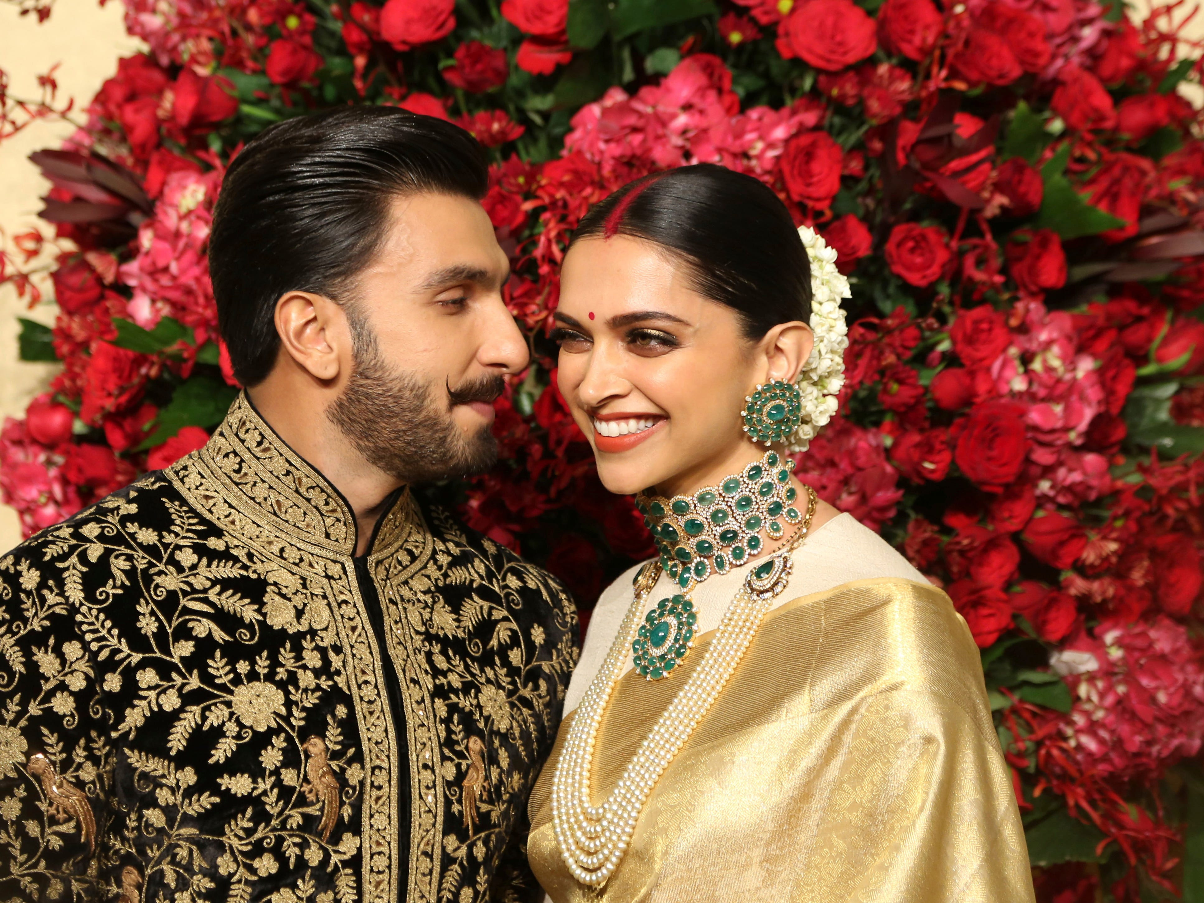 Bollywood actors Deepika Padukone, right, and Ranveer Singh pose at their wedding reception in Bangalore, India, Wednesday, Nov. 21, 2018. The couple got married at Villa Balbianello, a lakeside mansion featured in Star Wars and James Bond films in Lenno, Como lake, northern Italy on Nov. 14, 2018.