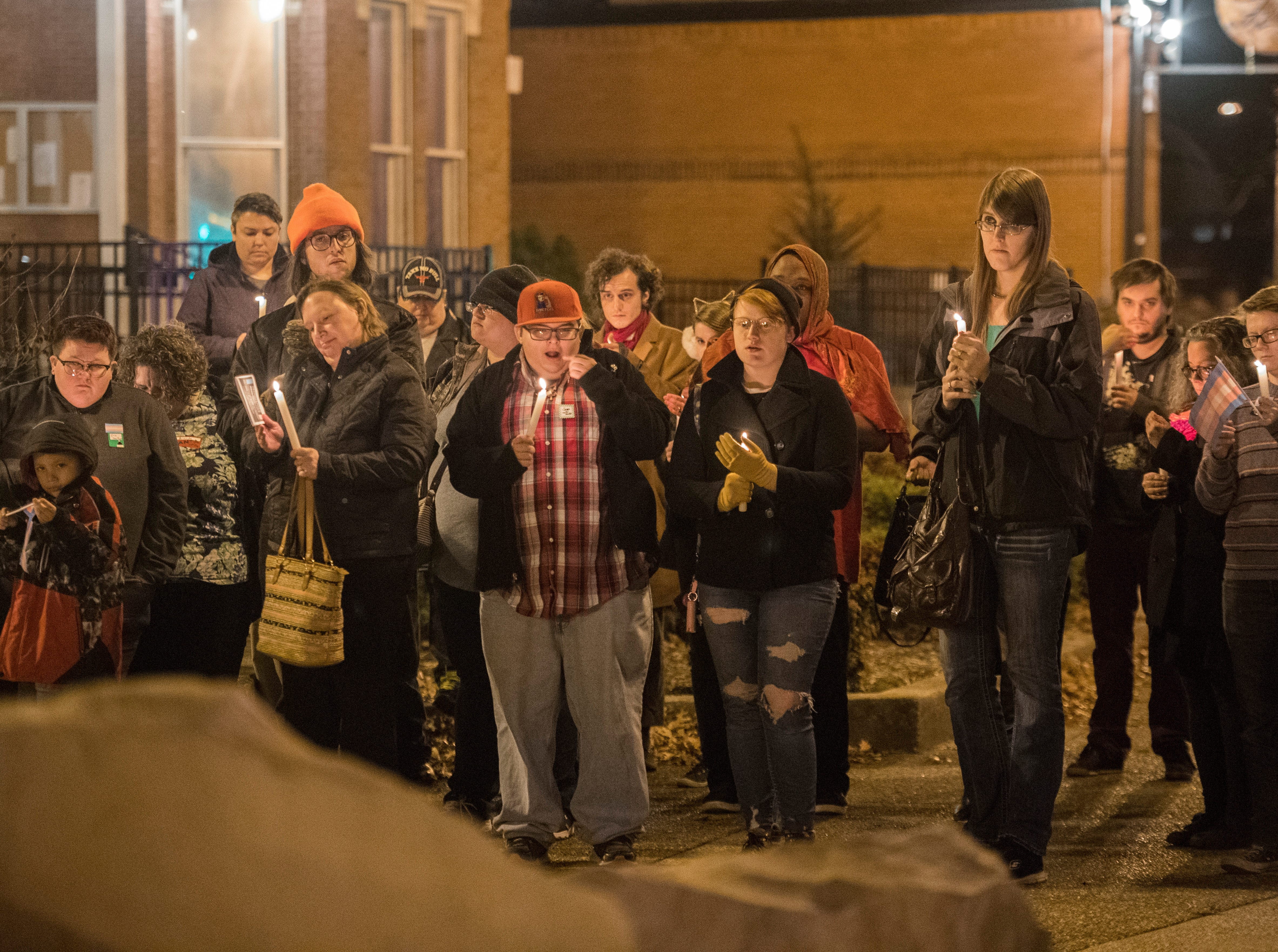 A group takes a moment of silence during the candlelight vigil for Transgender day of Remembrance on Haynie's Corner Tuesday, Nov. 20, 2018.